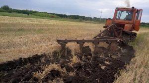 Обработка земли с помощью плуга к трактору ДТ-75