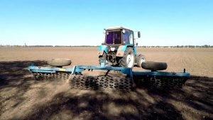 Процесс прикатывания почвы катком