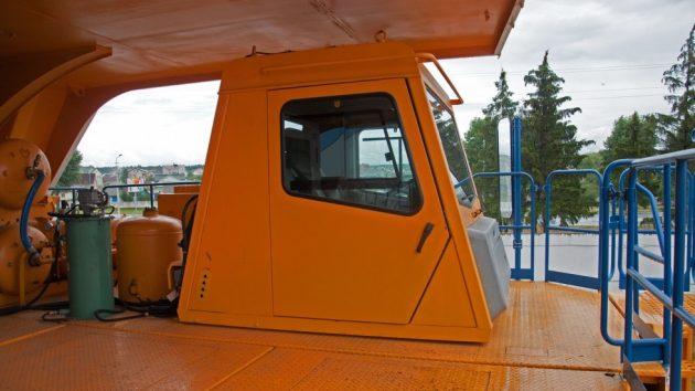 За кабиной находятся части объединённой гидравлической системы (рулевого управления, тормозной системы и опрокидывающего механизма)